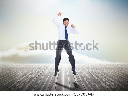 Businessman jumping over wooden boards leading out to the horizon with his fist in the air - stock photo