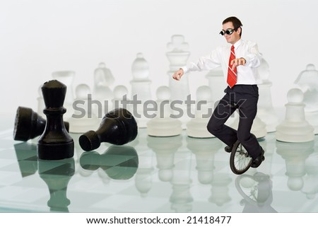 Businessman keeping his balance riding a mono cycle on a chess board - stock photo