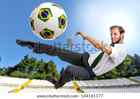Businessman kicking a soccer ball - stock photo