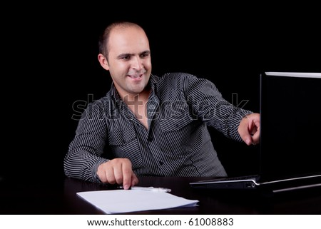 businessman laughing looking to computer, isolated on black background. Studio shot. - stock photo