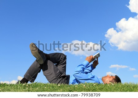 businessman laying down on the grass and working with tablet - stock photo