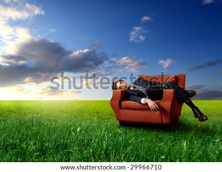 businessman laying on an armchair in a grass field - stock photo