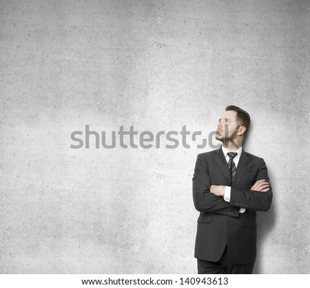 businessman leaning against a concrete wall and thinking - stock photo