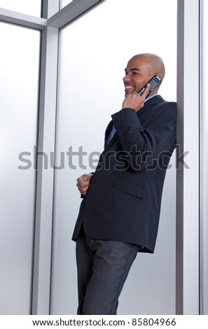 Businessman leaning against the window, talking on the phone and smiling. - stock photo