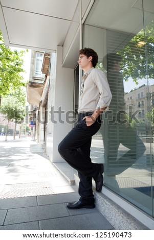 Businessman leaning on an office buildings glass window in the city with his hands in his pockets, waiting. - stock photo