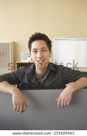 Businessman leaning on cubicle wall - stock photo