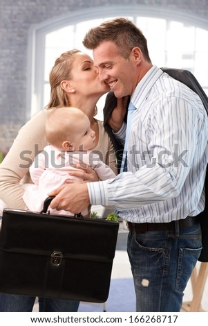 Businessman leaving for work, wife and baby daughter saying good-bye to him. - stock photo