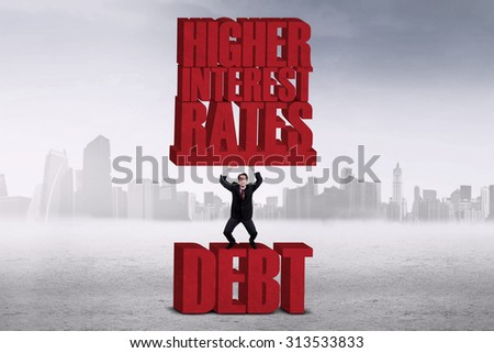 Businessman lifting HIGHER INTEREST RATES words while standing on the word DEBT - stock photo
