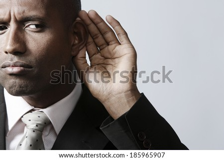 Businessman listening with hand on ear - stock photo