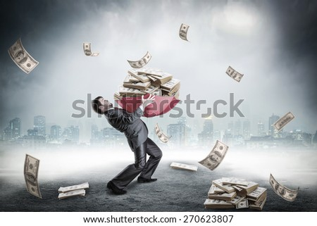 Businessman loaded with huge amount of money - stock photo