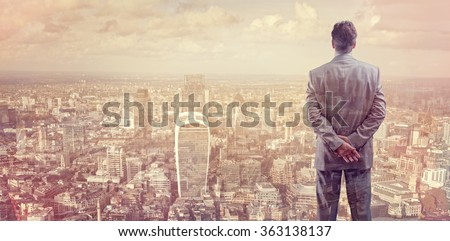 Businessman looking across the city of London financial district concept for entrepreneur, leadership and success - stock photo