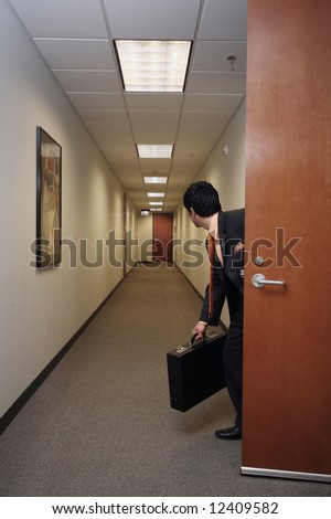 Businessman looking around suspiciously with his briefcase in hand in an empty hallway - stock photo