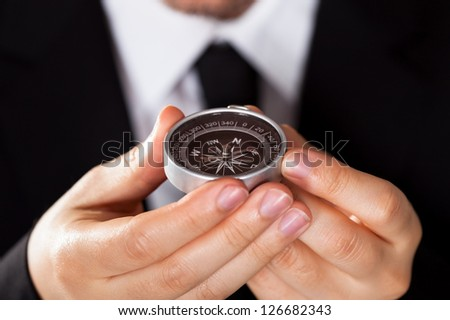 Businessman looking at a compass which he is holding in his hand with focus to the compass - stock photo