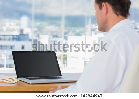 Businessman looking at a laptop in his office - stock photo