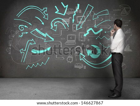 Businessman looking at a wall with drawings of arrows and chart on it - stock photo