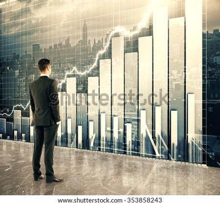 Businessman looking at big screen with business graph - stock photo
