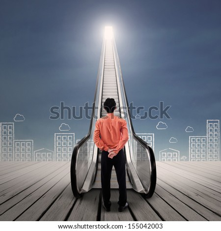 Businessman looking at bright escalator under blue sky - stock photo