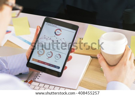 Businessman looking at business chart and drinking coffee in office - stock photo