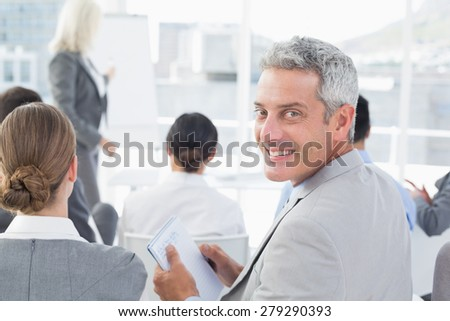 Businessman looking at camera during meeting in meeting room - stock photo