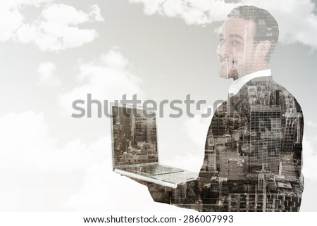 Businessman looking at camera holding laptop against new york skyline - stock photo