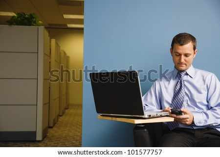 Businessman looking at cell phone - stock photo