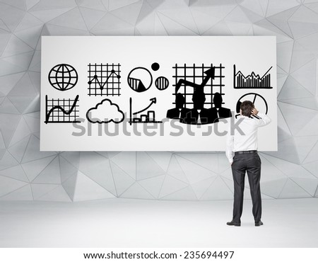 businessman looking at drawings of business concept on whiteboard - stock photo