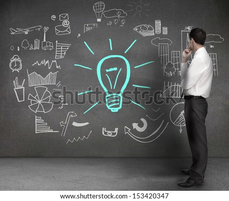 Businessman looking at drawings on a wall with a light bulb and different charts - stock photo