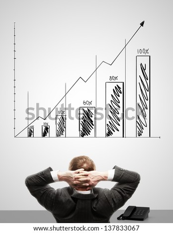 businessman looking at graph on wall - stock photo
