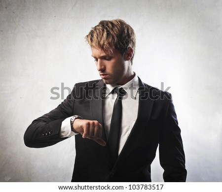 Businessman looking at his wristwatch - stock photo