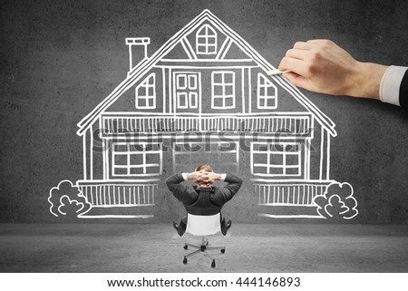 Businessman looking at house being drawn while relaxing on chair. Concrete background. Concept of mortgage and real estate - stock photo