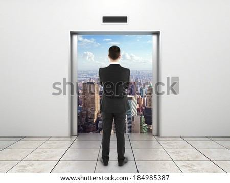 businessman  looking at modern elevator with opened door to city - stock photo