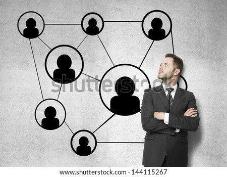 businessman looking at social media icons drawing on concrete wall - stock photo