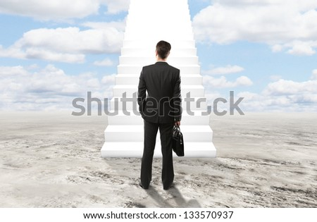 businessman looking at stairs to heaven - stock photo