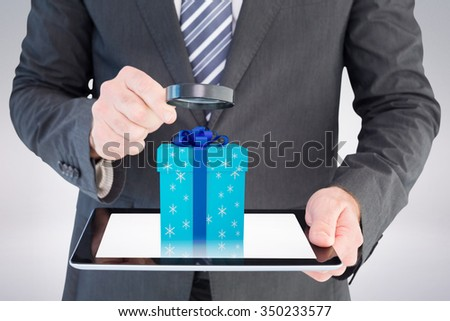 Businessman looking at tablet with magnifying glass against blue and silver gift box - stock photo