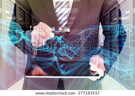Businessman looking at tablet with magnifying glass against server room with towers - stock photo