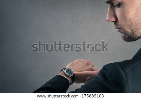Businessman looking at the time on his wrist watch against dark grunge background with copy space. - stock photo