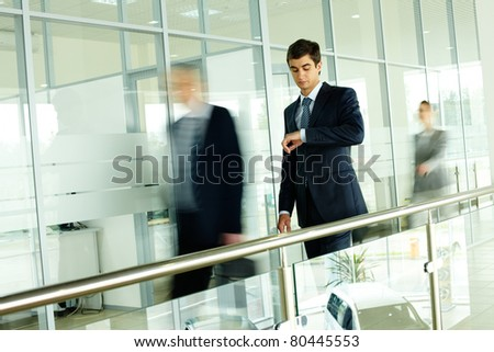 Businessman looking at watch with walking people on background - stock photo