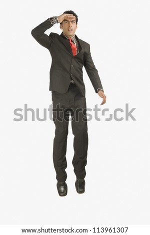 Businessman looking away with shielding his eyes - stock photo