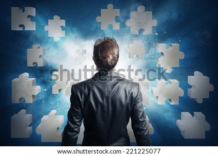 Businessman looking for the solution of the puzzle - stock photo