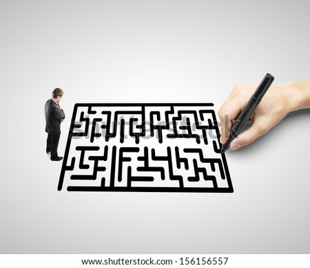 businessman looking like a hand drawing a maze - stock photo