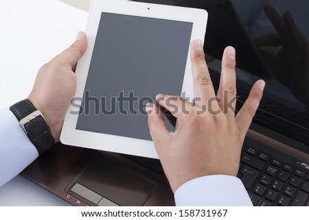 Businessman looking over electronic tablet - stock photo