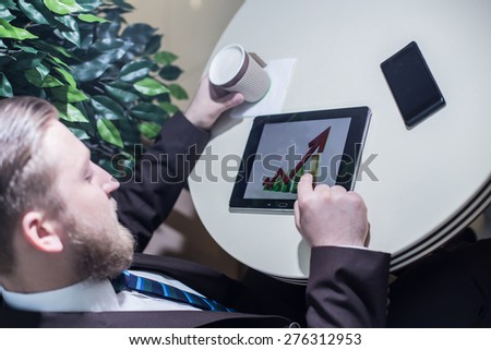 Businessman looking, phone, coffee, growth chart, success - stock photo