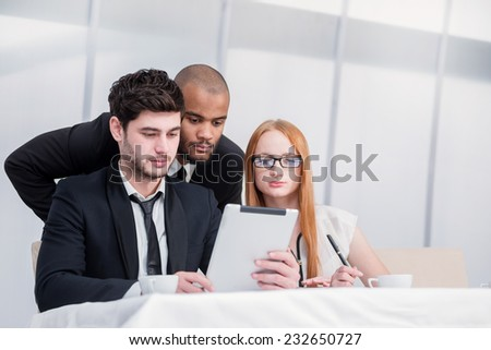 Businessman looking report within the tablet. Young man holding tablet in hand while his colleagues look into the tablet. Businesspeople sitting at a table at a meeting in the office. - stock photo