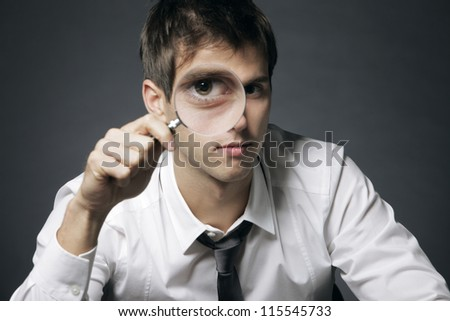 businessman looking through a magnifying glass - stock photo