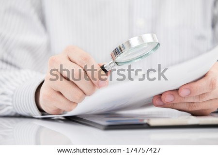 Businessman looking through a magnifying glass to documents - stock photo
