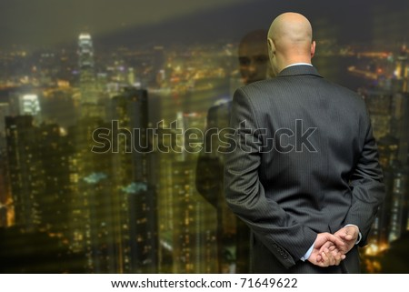 Businessman looking through a window to the city lights - stock photo