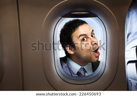 Businessman looking  through an airplane window - stock photo