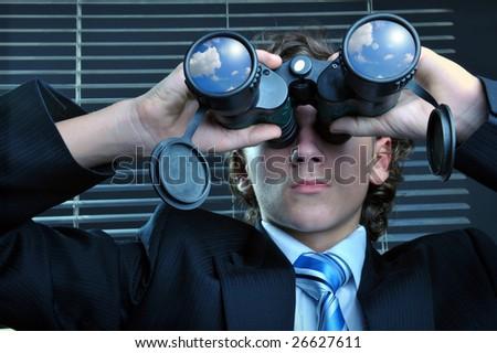 Businessman looking through binoculars, sky reflection on lens - stock photo