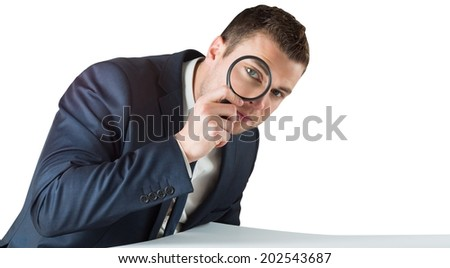 Businessman looking through magnifying glass on white background - stock photo