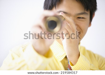 Businessman looking through telescope - stock photo
